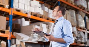 Warehouse organization by worker with clipboard